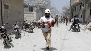 Un miembro de la defensa civil leva en brazos a una niña herida tras los bomberdeos en Marat al Noomane.