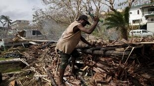 Un ouvrier tronçonne un arbre déraciné par le passage du cyclone. Port-Vila, le 19 mars 2015.