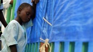 A child with cholera symptoms waits to receive treatement at a Port-au-Prince hospital