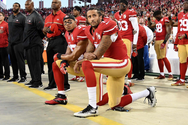 Colin Kaepernick (à direita) e Eric Reid (à esquerda) ficam de joelhos durante execução do hino, antes de um jogo da NFL em setembro de 2016.