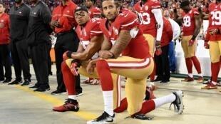 Colin Kaepernick (à droite) et Eric Reid (à gauche) posant un genou à terre lors de l'hymne américain, le 12 septembre 2016, avant un match de NFL