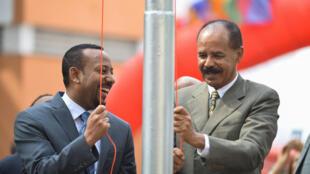 Le président érythréen Isaias Afwerki et le Premier ministre éthiopien Abiy Ahmed hissent le drapeau érythréen lors d'une cérémonie d'inauguration marquant la réouverture de l'ambassade d'Érythrée à Addis-Abeba, le 16 juillet 2018.