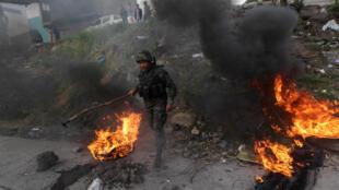 Un soldado quita neumáticos en llamas colocados por la oposición en medio de protestas por la elección presidencial, el 11 de diciembre en Tegucigalpa.