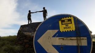 Un autocollant «No Border, No Brexit», «Pas de frontière, pas de Brexit» sur un panneau de signalisation devant la statue de la paix intitulée «Les mains du fossé» à Londonderry, en Irlande du Nord.