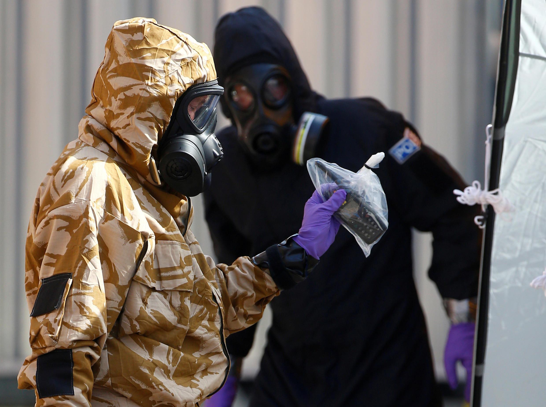 Investigadores forenses, usando roupas de proteção, saem de John Baker House, depois que foi confirmado que duas pessoas haviam sido envenenadas com o agente nervoso Novichok, em Amesbury, Inglaterra, em 6 de julho de 2018.