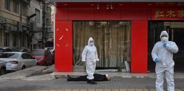 Một người đàn ông nằm bất động suốt hơn hai tiếng trên vỉa hè mới có đội ngũ y tế đến chở đi.                                                                                                                             Ảnh chụp ngày 30/01/2020 tại Vũ Hán..