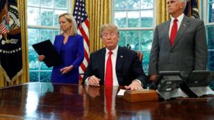 La secretaria de Defensa Nacional, Kirstjen Nielsen, recibe la orden ejecutiva que impide la separación de niños en la frontera entre México y Estados Unidos. El vicepresidente Mike Pence presencia la firma, en la Casa Blanca en Washington.
