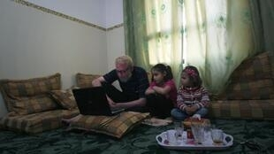 Un réfugié palestinien de retour de Syrie, aux côtés de ses deux filles dans un appartement de location à Gaza, le 16 avril 2013.