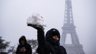 Neve vira brincadeira para as crianças ao lado da Torre Eiffel. 05/02/18