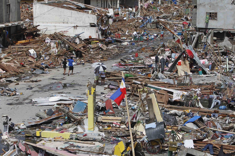 Sobreviventes caminham em meio aos destroços após passagem do supertufão Haiyan em Tacloban, no centro das Filipinas.
