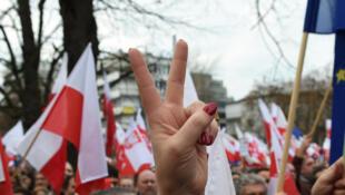 Une manifestante faisant le signe de la victoire lors d'une manifestation anti-gouvernementale, le 19 décembre 2015 à Varsovie.