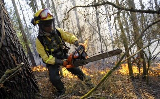 Um bombeiro tenta apagar o incêndio perto de A Capela, na Galícia, no norte da Espanha, no domingo, 1 de abril.