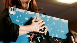 Argentine President Cristina Fernandez de Kirchner holds a picture of herself and  late husband while celebrating her victory in Argentina's presidential election.