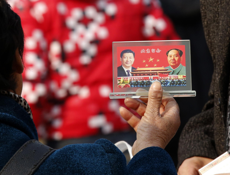Một người bán sách trên quảng trường Thiên An Môn (Bắc Kinh) khoe hình ảnh hai ông Tập Cận Bình và Mao Trạch Đông, ngày 08/11/2012, trước đại hội đảng Cộng Sản Trung Quốc.