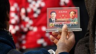Un vendeur de rue montre une photo du président chinois actuel Xi Jinping et de Mao Mao Tsé-toung, le 8 novembre 2013, à la veille de l'ouverture du Plénum du Parti communiste chinois, sur la place Tienanmen.