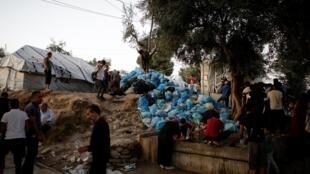 Des migrants du camp de Moria remplissent des bouteilles d'eau à côté d'une pile de déchets sur l'île de Lesbos, le 2 octobre 2019.