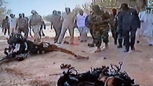 Imagem de uma televisão do Sahel mostrando homens observam os restos do veículo que explodiu no atentado suicida perpetrado em Agadez, no norte do Níger, na quinta-feira, 23 de maio de 2013.