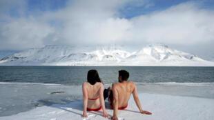 Ativistas fazem protesto diante de calota polar para alertar sobre os riscos do aquecimento do planeta.
