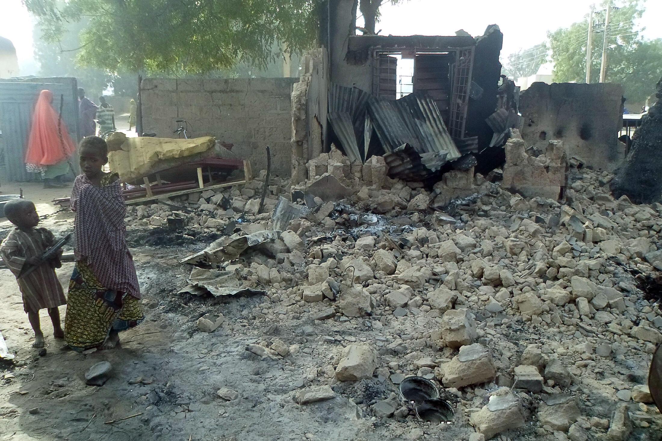 Deux enfants devant les décombres d'une maison détruite lors de l'attaque de Boko Haram dans le village de Dalori, près de Maiduguri (nord-est du Nigeria). Au moins 85 personnes ont été tuées dans cette attaque menée samedi 30 janvier 2016.