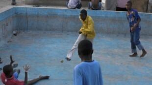 Des enfants haïtiens, vivant dans un camp de tentes, jouent avec une balle de tennis, à Port-au-Prince, le 22 novembre 2011.
