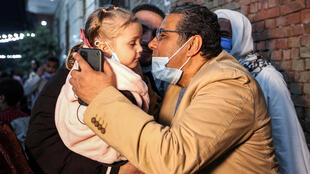 Mahmoud Hussein kisses a child upon his arrival at his family home in greater Cairo after four years in jail in Egypt