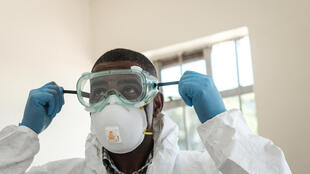Laboratory technician gets ready with filtered mask, goggles and gloves at Infectious Disease Unit of Kenyatta National Hospital in Nairobi, Kenya, on 15 March 2020.