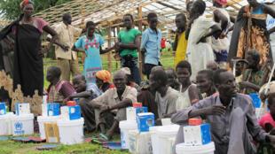 Le 18 juin 2017, des déplacés sud-soudanais dans le camp de Bentiu reçoivent des vivres distribués par l'ONU.