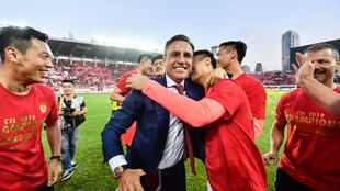 Guangzhou Evergrande's head coach Fabio Cannavaro celebrates with his players and after winning the Chinese Super League last season. They will now be able to begin their delayed title defence from July 25