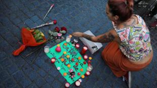 """Mulher deixa velas e cartaz escrito """"Catalunha, lugar de paz"""" no local onde a van atropelou pedestres nas Ramblas, em Barcelona, 18 de agosto de 2017."""