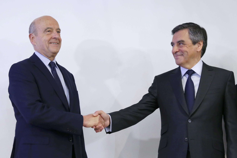 Ален Жюппе (слева) и Франсуа Фийон пожимают руки после объявления результатов второго тура праймериз правых и центристов, Париж, 27 ноября 2017 г.