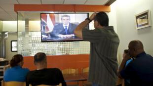 En un restaurant, los clientes escuchan el discurso del gobernador Alejandro Garcia Padilla sobre la deuda, San Juan, 29 de junio de 2015.
