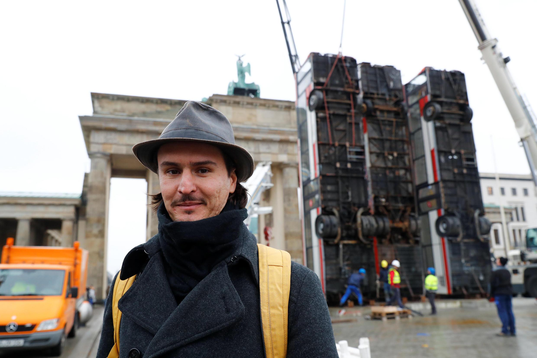 L'artiste germano-syrien Manaf Halbouni, l'auteur de « Monument », lors de l'installation de son oeuvre le 10 novembre devant la porte de Brandebourg à Berlin.