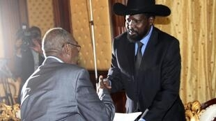 South Sudan Referendum Commission chair Mohamed Ibrahim Khalil (L) gives  the results to Sudan's VP Salva Kiir