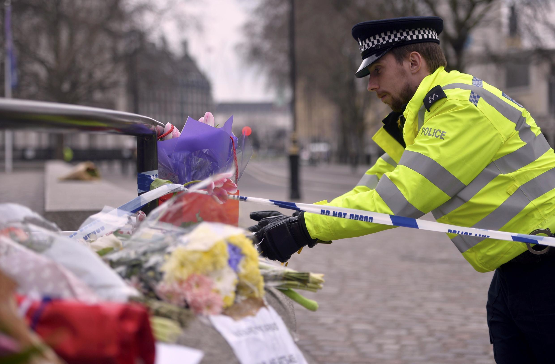 Agente da polícia deposita flores em frente ao Palácio de Westminster 23/03/17