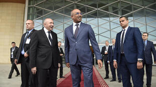 French Minister of Interior Gerard Collomb (C-L) and his Algerian counterpart Noureddine Bedoui (C) stand outside after chairing a meeting in Algiers on March 15, 2018.
