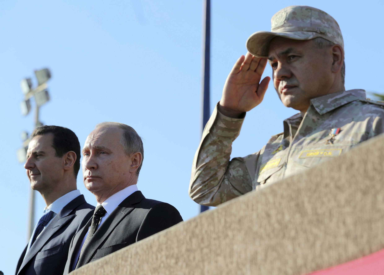 Президент России Владимир Путин (в центре), министр обороны РФ Сергей Шойгу (справа) и президент Сирии Башар Асад на военной базе Хмеймим, 11 декабря 2017.