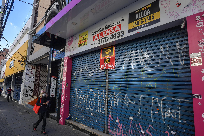 Una mujer camina delante de locales comerciales cerrados en una calle de Sao Paulo,  el 17 de junio de 2020
