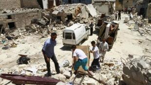 Ces habitants ont perdu leurs habitations lors d'un récent bombardement. Ils tentent de récupérer les biens restés parmi les décombres.