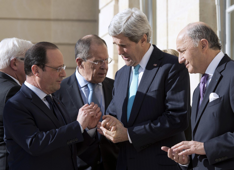 O presidente francês, François Hollande, recebe o secretário de Estado americano, John Kerry, e o chanceler russo, Serguei Lavrov (ao fundo), no Palácio do Eliseu, em Paris.