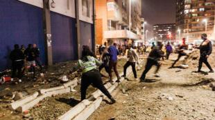 Agentes de la policía detienen a unos saqueadores en el centro de Durban durante la protestas callejeras, el 11 de julio de 2021 en la ciudad sudafricana
