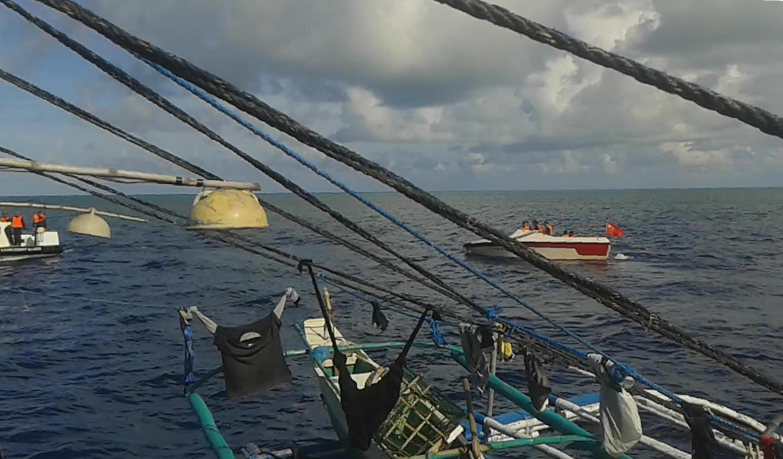 Ảnh một ngư dân Philippines chụp từ điện thoại di động ngày 07/06/2016 cho thấy Hải Cảnh Trung Quốc dùng thuyền cao tốc (phía sau bên trái và bên phải) để chặn đường một tàu cá Philippines tại vùng bãi cạn Scarborough.