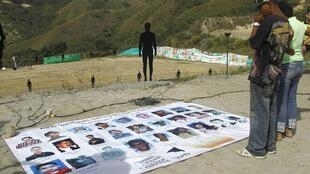 """Familiares de desparecidos buscan fotos de los suyos durante una ceremonia en """"La Escombrera"""" en Medellín, Colombia el 27 de julio  2015."""