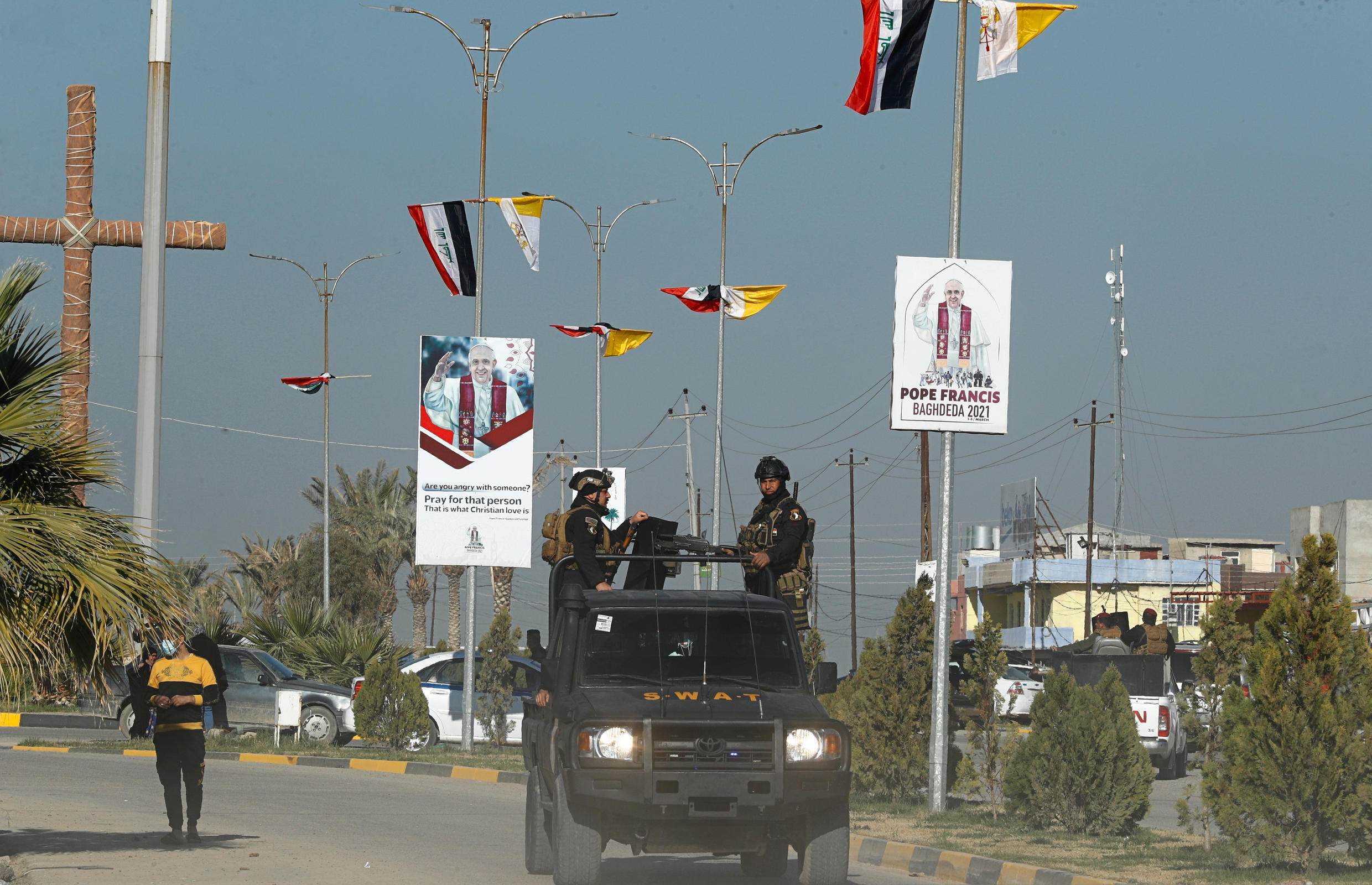 Iraqi security forces pass by Iraq and the Vatican flags and posters announcing visit of the Pope Francis in a street in Qaraqosh, Iraq, Monday, Feb. 22, 2021. Iraq was estimated to have more than 1 million Christians before the 2003 U.S.-led invasion that toppled dictator Saddam Hussein.  Now, church officials estimate only few hundred remain within Iraq borders. The rest are scattered across the globe, resettling in far-flung places like Australia, Canada and Sweden as well as neighboring countries.