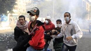 Des manifestants transportent un blessé près du ministère de l'Intérieur au Caire, mercredi 23 novembre 2011.