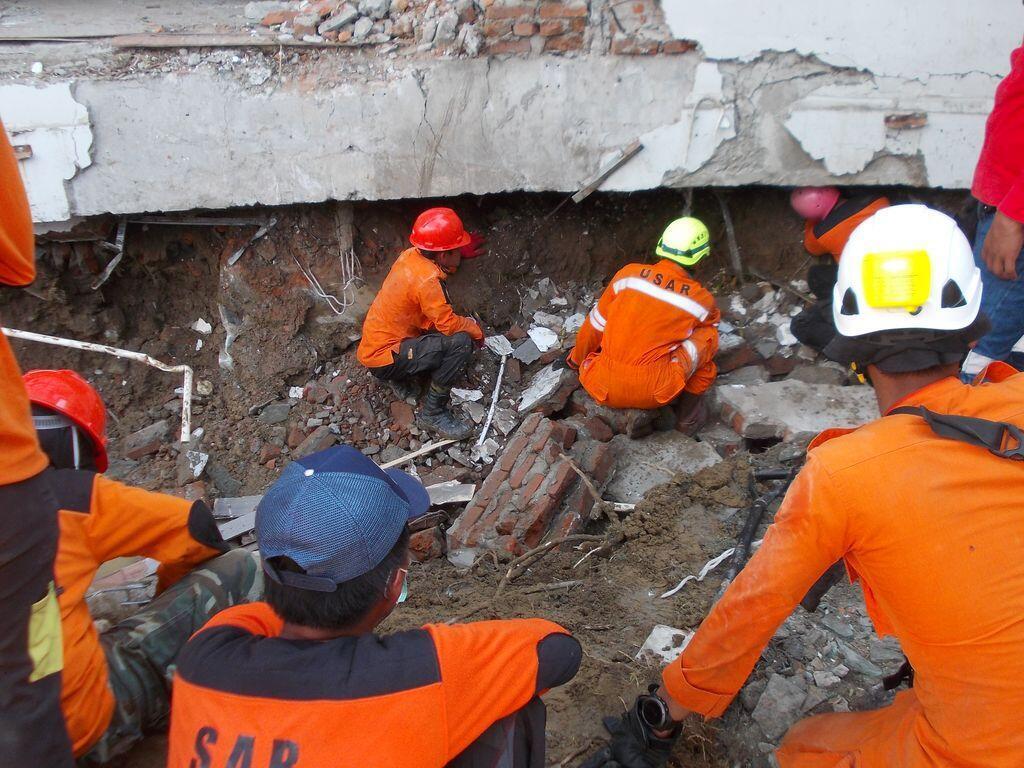Recherches dans les décombres de l'hôtel Mercure de Palu.