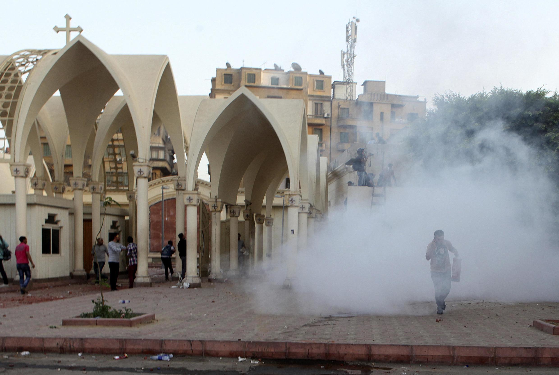 Những người Công giáo chạy vào bên trong nhà thờ chính tòa  ở Cairo, trong lúc cảnh sát bắn hơi cay trong các vụ xung đột với người Hồi giáo bên ngoài nhà thờ, ngày 07/04/2013.