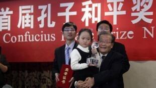 Une petite fille tient dans les mains le premier « prix Confucius pour la paix  » remis à Lien Chan, ce jeudi 9 décembre 2010, à Pékin.