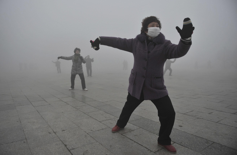 Mulheres chinesas fazendo exercícios mas usando máscaras para se proteger da poluição.