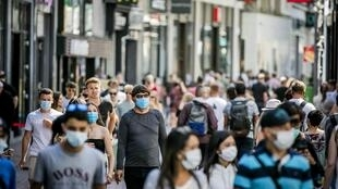 People, wearing a face mask, walk in the Kalverstraat, in Amsterdam on August 5, 2020, from when wearing a face mask is mandatory in five usually crowded places in the city of Amsterdam
