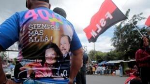 """Apoiador do presidente da Nicarágua, Daniel Ortega, celebra os 40 anos da """"Repleiegue"""" em Manágua."""